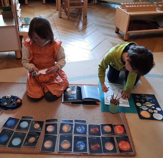 Two children working on the floor to match the shapes and colours of the planets.