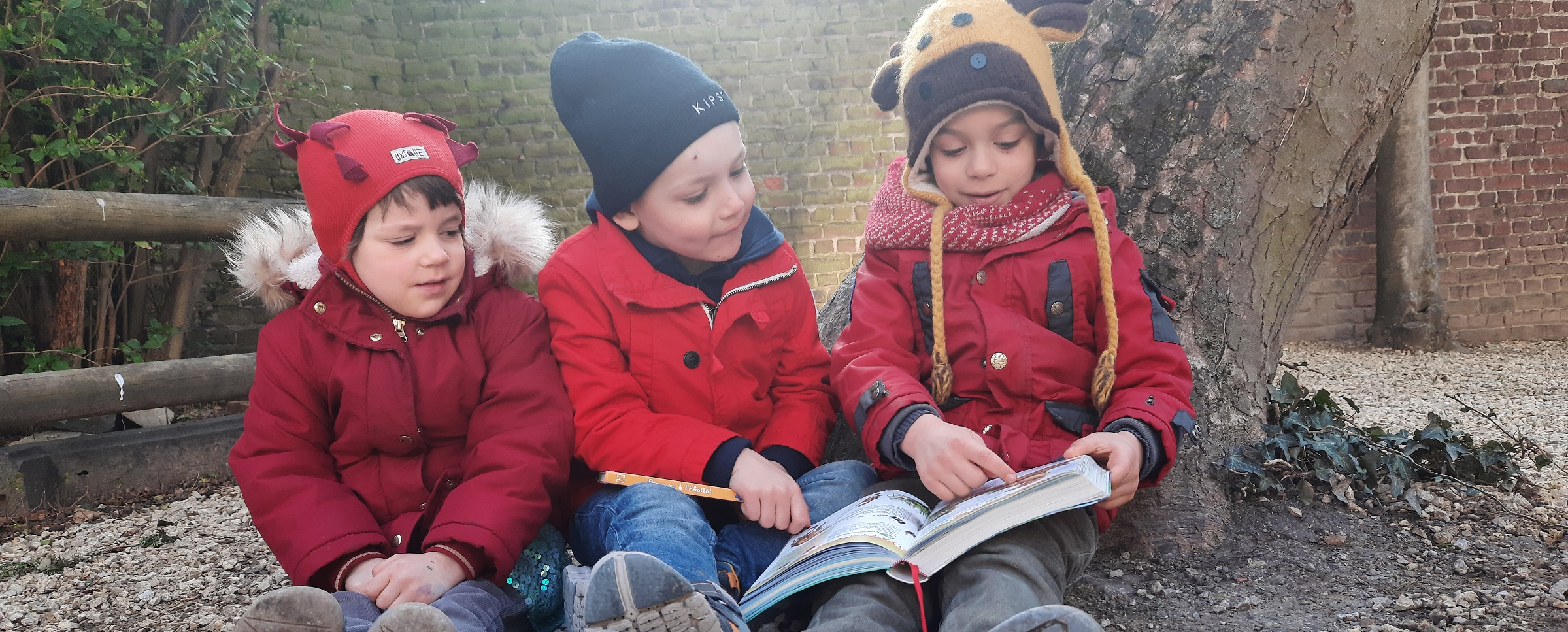 Three children sitting on the ground and one of them showing something in a book to the other two.