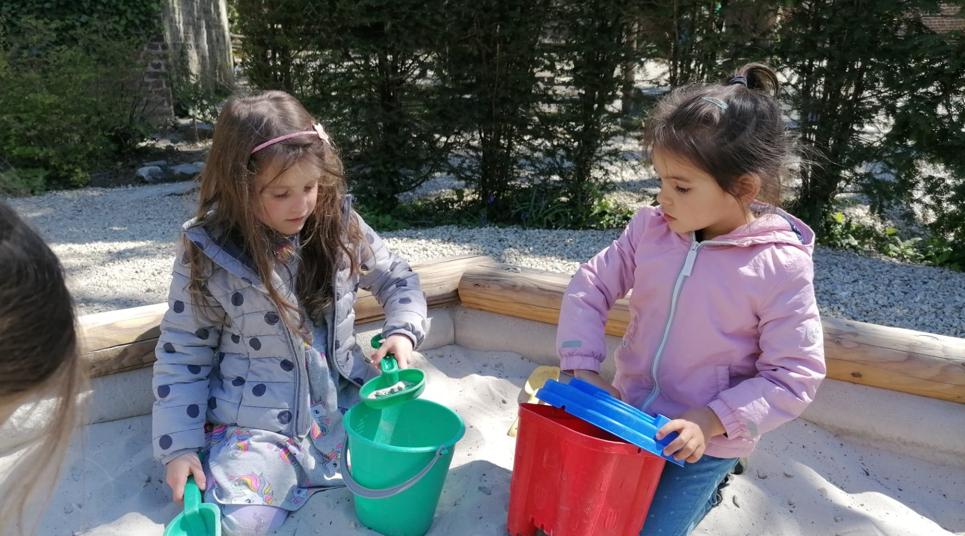 Two children playing in the sandpit.