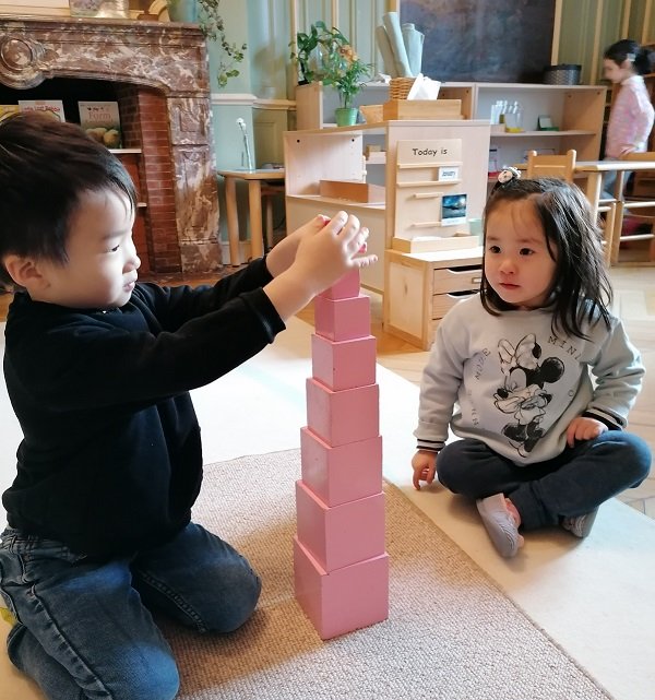 Two children working together to create a pyramid structure.
