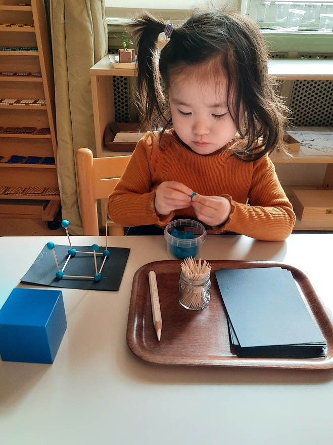 A young girl creating a shape with playdough and matchsticks.