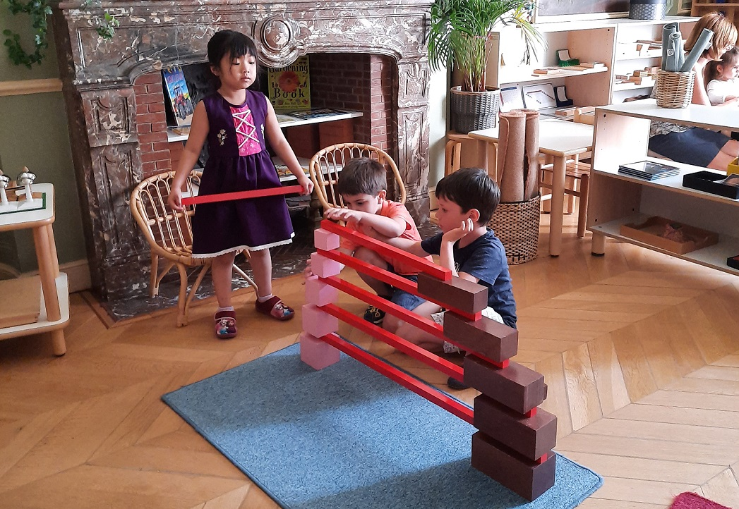 Three children working together to create a series of bridge structures.