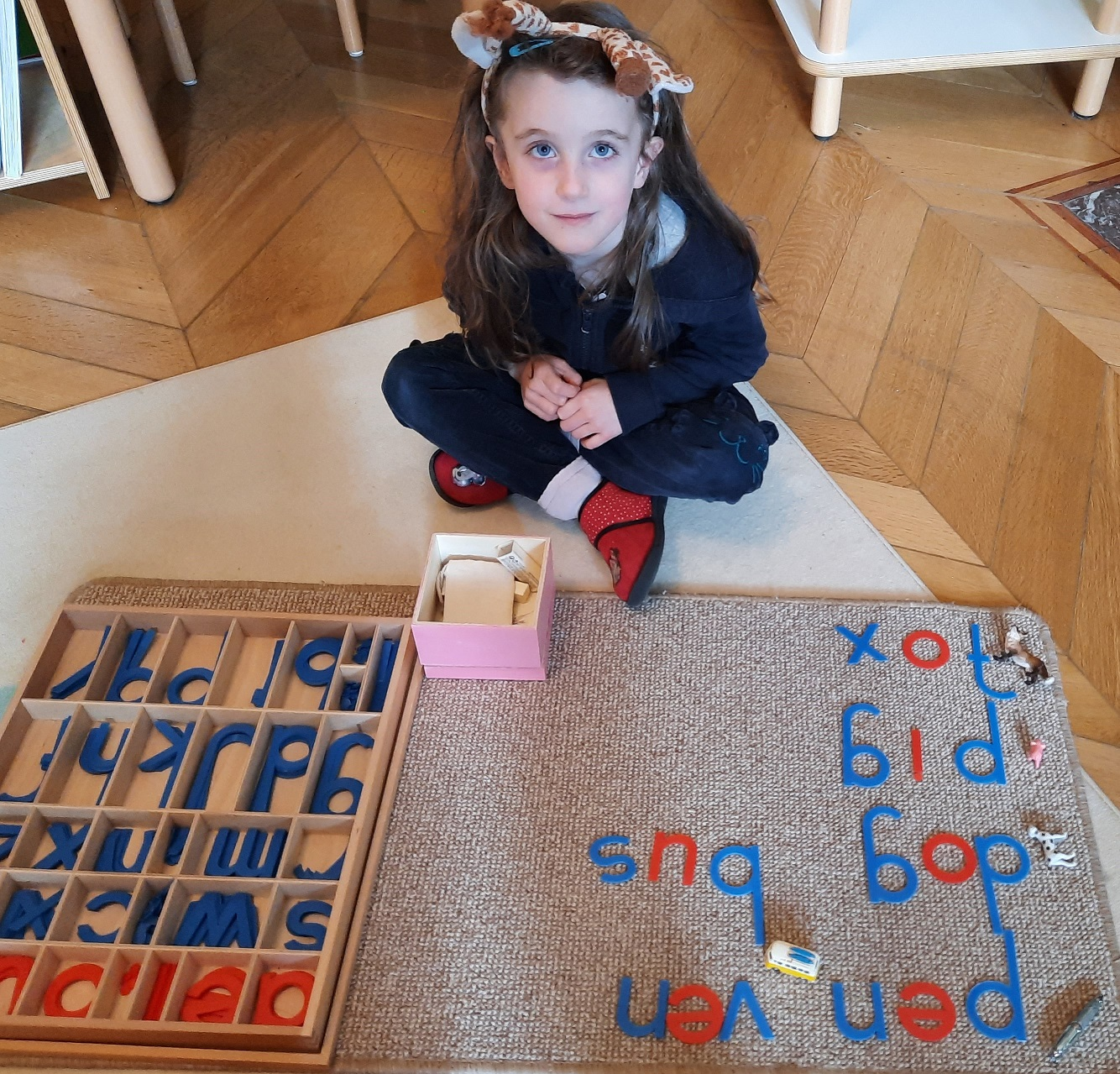 A child learning to spell with letter forms on the floor.