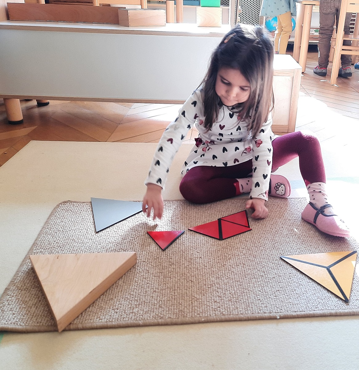A child matching shapes to make larger shapes.
