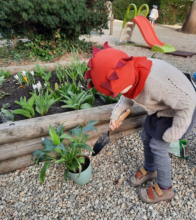 A child planting plants in the garden.