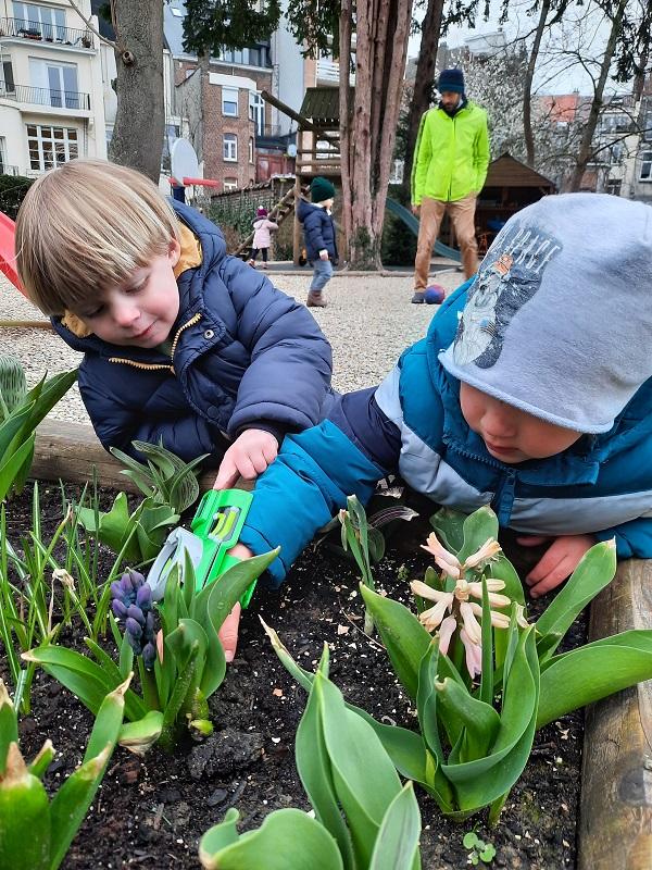 Two boys learning to plant seeds in the garden.