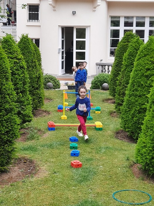 Children in a line preparing to complete an obstacle course in the garden.