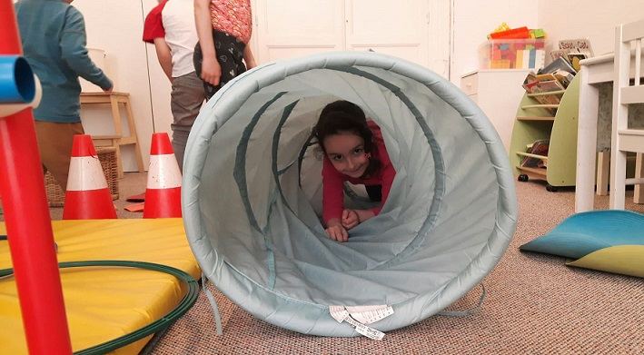 A young girl crawling through a tube as part of gym class.