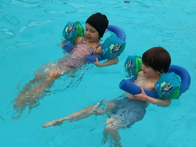 Two children swimming using floats.